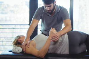 Chiropractor giving shoulder pain therapy to female patient.