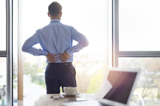 a man standing and having a lower back pain