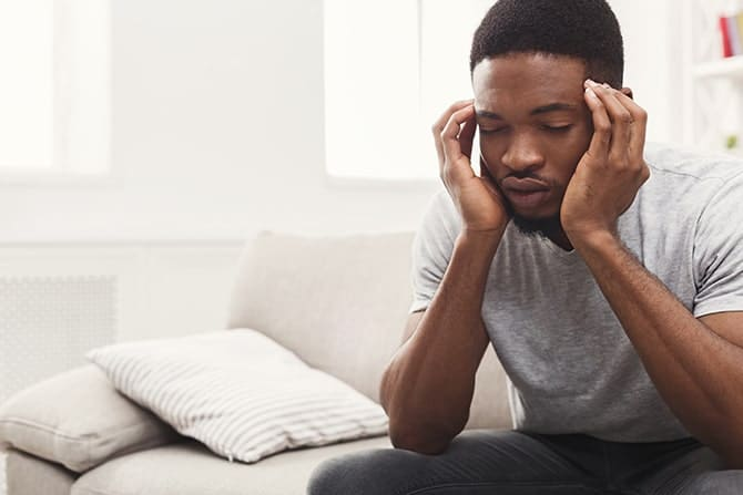 a man sitting an having a headache