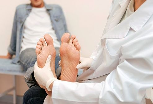 a chiropractor examining a patience for Neuropathy Symptoms