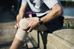 Adult man sitting on a side walk holding his knee due to pain. Stem cell therapy treatment can help relieve the pain.