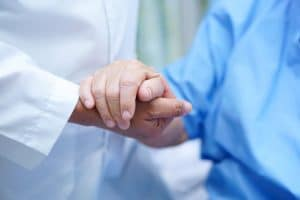 Patient and doctor holding hands after a pain management procedure